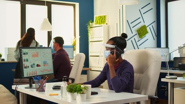 Empreendedor africano com máscara protetora e viseira fazendo negociações financeiras por telefone enquanto colegas fazem pesquisas estatísticas. colegas de trabalho multiétnicas trabalhando respeitando a distância social.