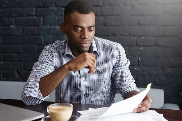 Empreendedor africano de sucesso estudando documentos com olhar atento e concentrado