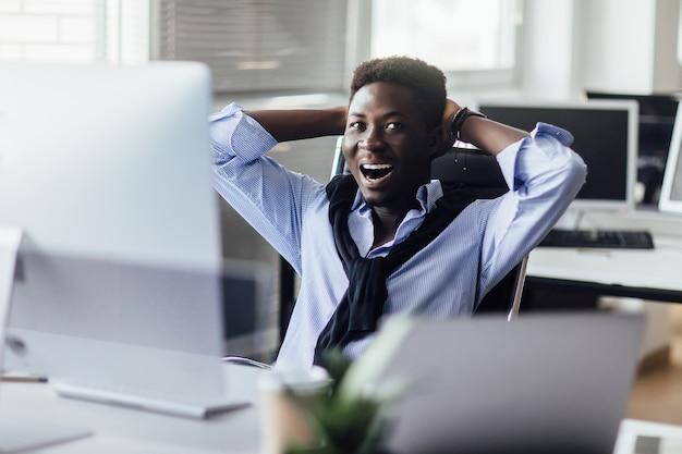 Empreendedor alegre neste escritório olhando para o monitor com um sorriso. emoções sinceras.