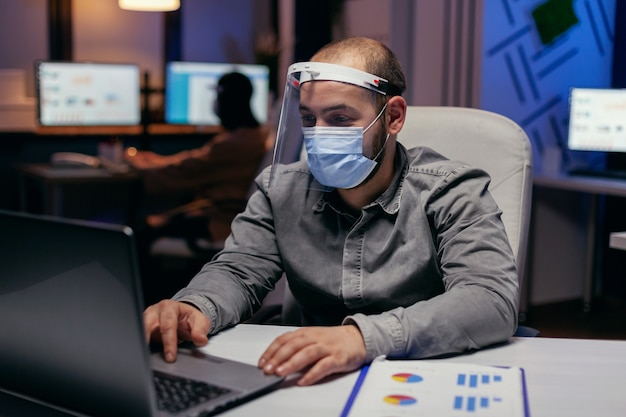 Empreendedor analisando relatórios de negócios no laptop usando viseira. homem estressado em uma corporação trabalhando duro para terminar um projeto usando máscara facial como medida de segurança devido à pandemia de coronavírus.