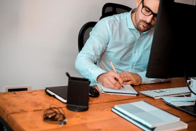 Empreendedor, anotando notas enquanto está sentado na mesa do escritório.
