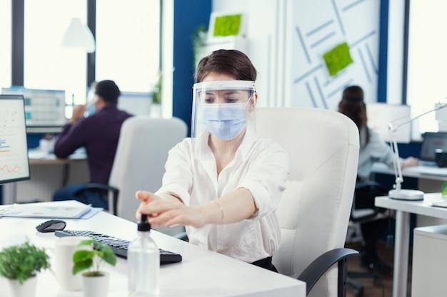 Empreendedor aplicando desinfetante para as mãos em uma pandemia global de coronavírus usando máscara e protetor facial. mulher de negócios em um novo local de trabalho normal, desinfetando enquanto colegas trabalhando em background