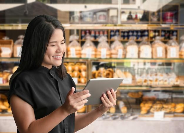 Empreendedor asiático ou proprietário de empresa feliz em trabalhar com um tablet digital no fundo de uma padaria