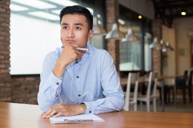 Empreendedor asiático pensando sobre o projeto em cafe