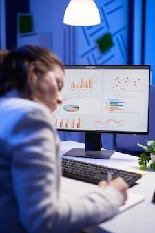 Empreendedor cansado tentando finalizar projeto empresarial durante videochamada na internet em frente ao computador, fazendo anotações em notebook