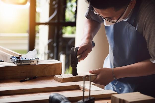 Empreendedor carpintaria segurando um martelo para montar as peças de madeira conforme o cliente solicitou