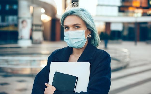 Empreendedor caucasiano de cabelos azuis segurando um laptop enquanto usa uma máscara branca especial e
