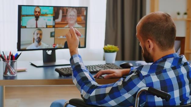 Empreendedor com deficiência em cadeira de rodas durante uma videoconferência.
