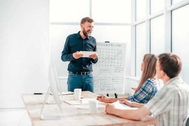 Empreendedor com tablet digital faz um relatório para a equipe de negócios. o conceito de trabalho em equipe