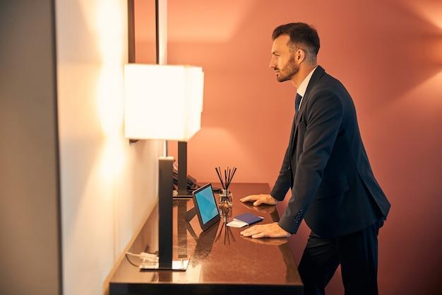 Empreendedor confiante e atraente colocando as mãos na cômoda e olhando seu reflexo em um espelho na zona do salão de negócios