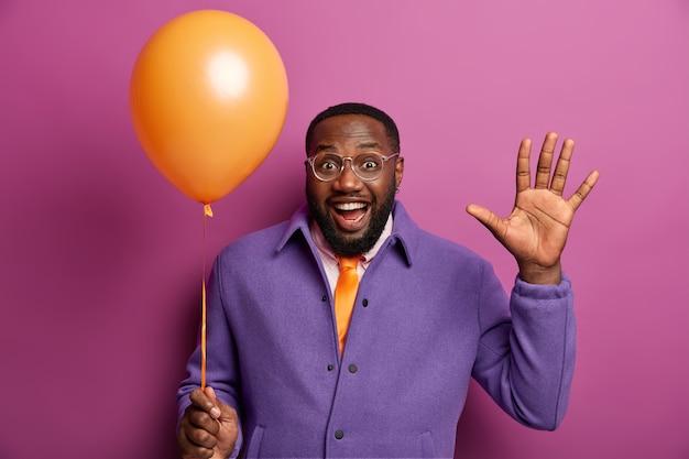 Empreendedor de homem de barba negra acena com a palma da mão, entra na festa corporativa, segura um balão de hélio inflado, gosta de um evento festivo em uma empresa de negócios, usa roupas formais, isolado na parede roxa