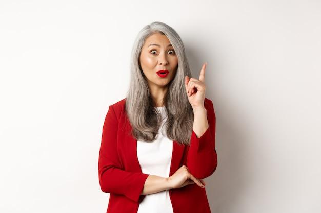 Empreendedor de idosa mulher asiática no blazer vermelho, tendo uma ideia, sugerindo algo, levantando o dedo em gesto de eureca, em pé sobre uma parede branca.