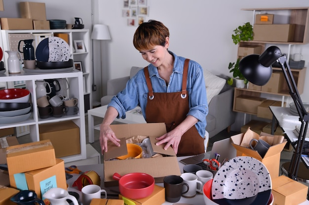 Empreendedor de mulher asiática madura, empresário de embalagem de produtos cerâmicos em embalagens para entrega e envio. conceito de trabalho em casa de venda online