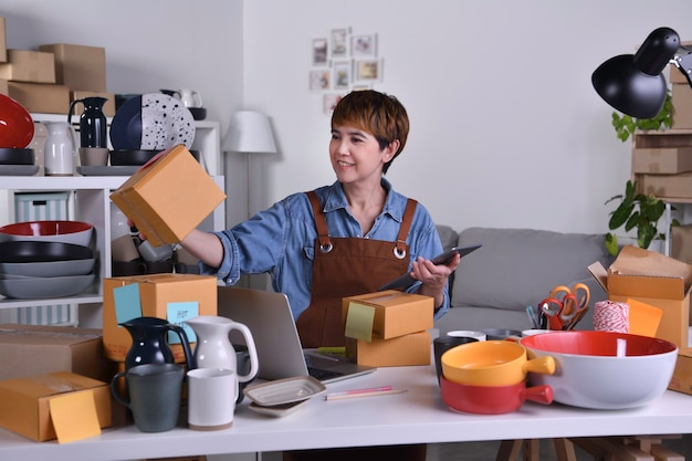 Empreendedor de mulher asiática madura, proprietário da empresa, verificando o endereço e os detalhes de entrega antes de enviar o produto. conceito de trabalho em casa de venda online