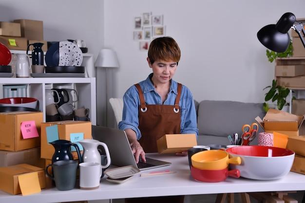 Empreendedor de mulher asiática madura, proprietário de uma empresa trabalhando no laptop, verificando o endereço e os detalhes de entrega antes de enviar o produto. conceito de trabalho em casa de venda online