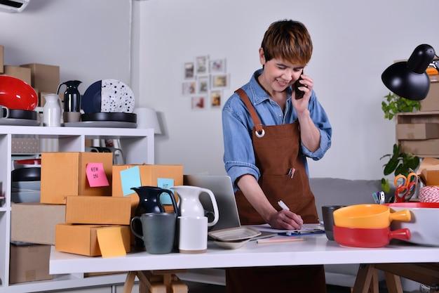 Empreendedor de mulher asiática madura, proprietário de uma empresa usando smartphone, verificando o endereço e os detalhes de entrega antes de enviar o produto. conceito de trabalho em casa de venda online