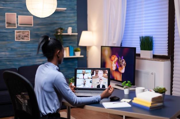 Empreendedor de pele escura consultando colegas remotamente de casa tarde da noite. usando moderna tecnologia de rede sem fio falando em reunião virtual fazendo hora extra.