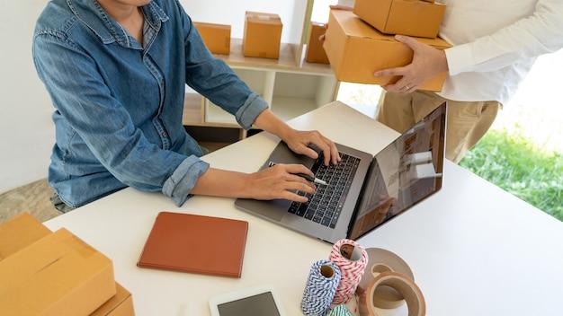 Empreendedor de pequena empresa iniciante, pme, jovem asiático trabalhando com um laptop