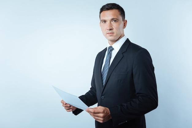 Empreendedor de sucesso. homem bonito e simpático e confiante segurando uma folha de papel e olhando para você em pé contra um fundo azul
