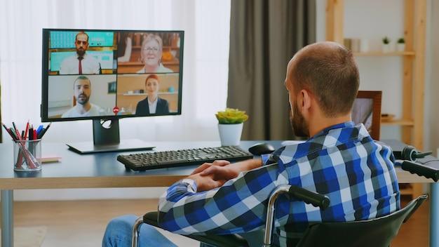 Empreendedor em cadeira de rodas se comunicando online com parceiros de negócios.