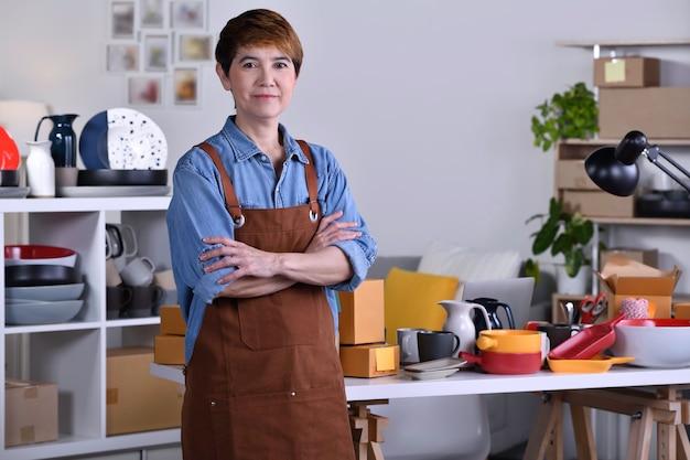 Empreendedor / empresário asiático maduro em frente ao seu produto de cerâmica de argila e trabalhando em casa