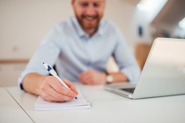 Empreendedor escrevendo notas sentado em sua mesa.