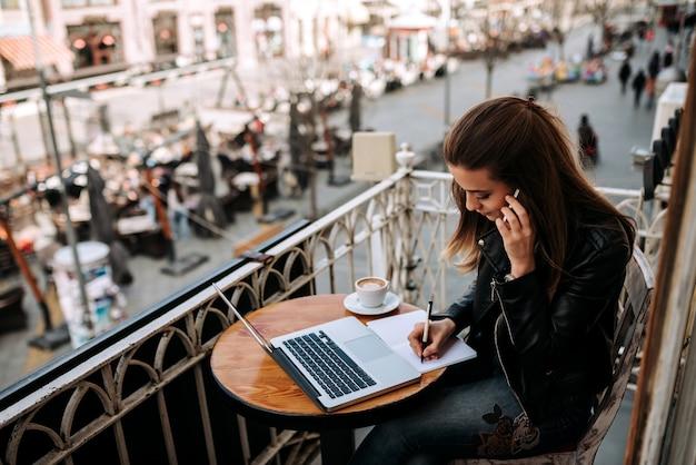 Empreendedor fêmea novo que trabalha ao ar livre. escrevendo em um notebook enquanto fala ao telefone.