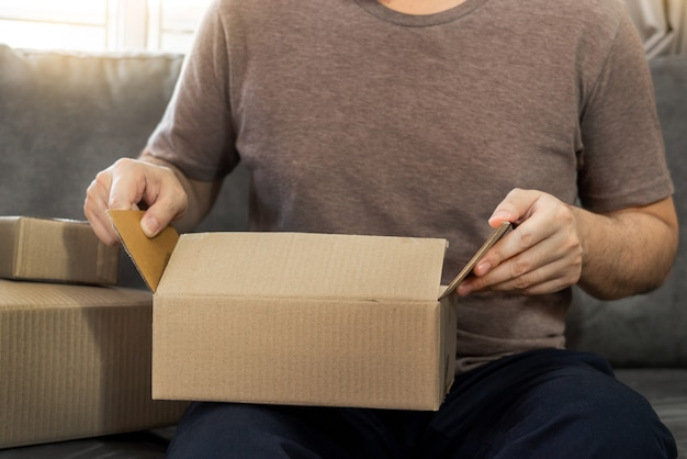 Empreendedor inicial de pequenas empresas, pme, jovem asiático trabalhando com laptop e caixa de embalagem de entrega