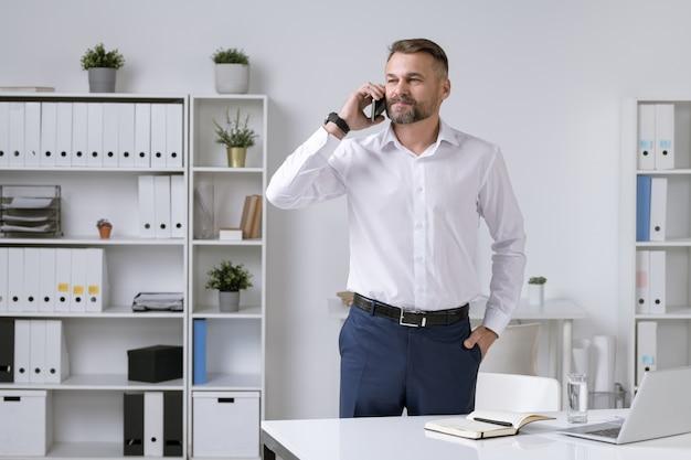 Empreendedor maduro, sério e confiante em trajes formais, segurando o smartphone pela orelha enquanto consulta o cliente ou parceiro de negócios