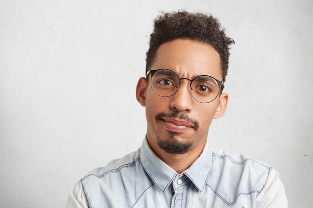 Empreendedor masculino sério com rosto oval, bigode e barba rala,