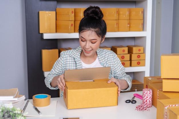 Empreendedor on-line de mulher embalagem caixa de encomendas no escritório em casa
