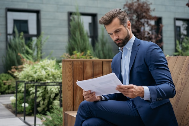 Empreendedor pensativo lendo contrato comercial ou relatório financeiro analisando documentos