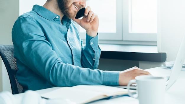 Empreendedor recortado e irreconhecível, ocupado, falando ao telefone celular no escritório