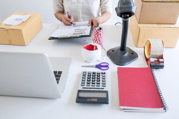 Empreendedor sme recebe cliente do pedido e trabalha com o mercado em linha da entrega da caixa do tipo do empacotamento