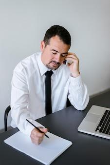Empreendedor trabalhando no telefone e escrevendo notas sentado em uma mesa no escritório