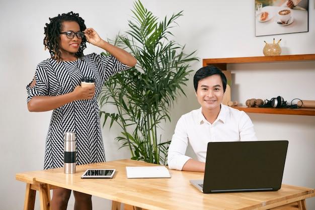 Empreendedor vietnamita sorridente trabalhando em um laptop, sua linda colega em pé perto da mesa com uma xícara de café para viagem e ajustando os copos