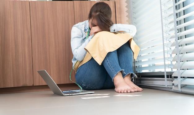 Empreendedora asiática estressada sentada ao lado da vitrine porque sua loja parou de funcionar
