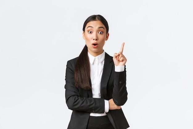 Empreendedora asiática inteligente e espantada, gerente de construção tem um ótimo plano, levantando o dedo para sugerir uma solução, compartilhando pensamentos e ideias com o grupo, fundo branco de pé