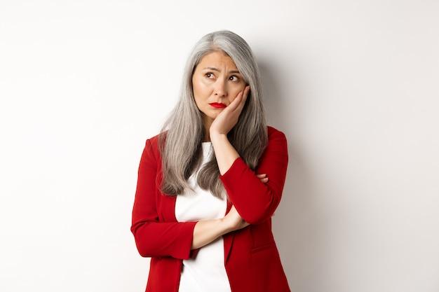 Empreendedora asiática preocupada e triste olhando para o canto superior esquerdo, pensando com uma expressão preocupada, em pé sobre um fundo branco