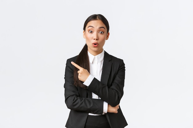 Empreendedora asiática surpresa e intrigada fazendo perguntas sobre o produto, permanecendo interessada, apontando o dedo para a esquerda para descobrir detalhes, discutindo o produto ou oferta com a equipe do escritório