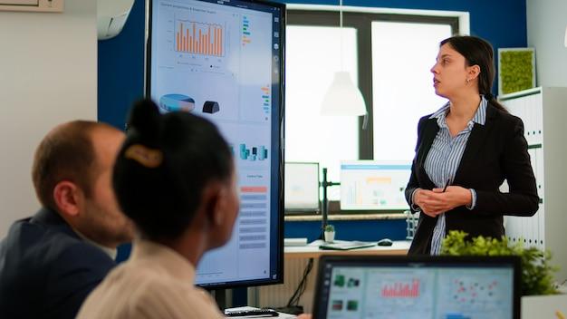 Empreendedora profissional discutindo sobre projeto com seus colegas, explicando a estratégia da empresa durante o brainstorming. equipe diversificada trabalhando em escritório financeiro de inicialização profissional durante a conferência