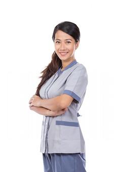 Empregada asiática bonita no braço cruzado uniforme