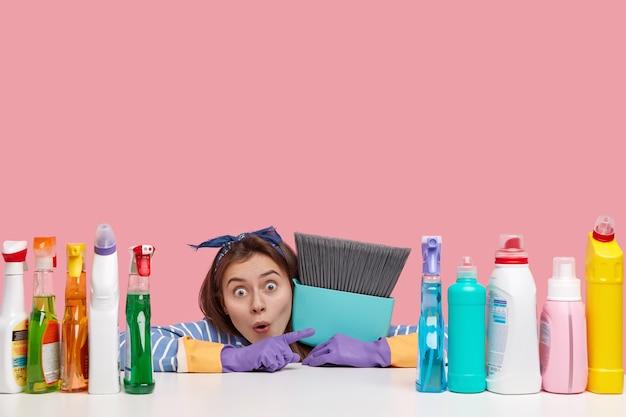 Empregada caucasiana estupefata aponta à parte, carrega a vassoura de perto, demonstra o resultado da limpeza do quarto sujo