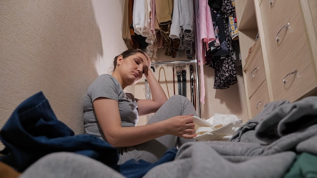 Empregada chateada olhando para roupa suja no chão do closet
