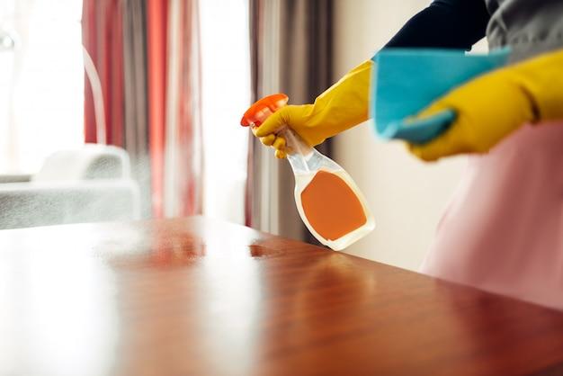 Empregada com as mãos nas luvas limpa a mesa com um spray de limpeza, interior de quarto de hotel