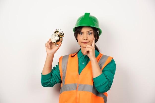 Empregada com capacete e segurando um relógio