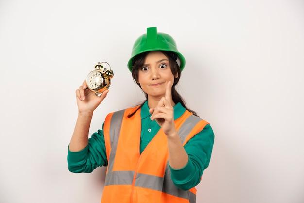 Empregada com o polegar para cima e segurando um relógio
