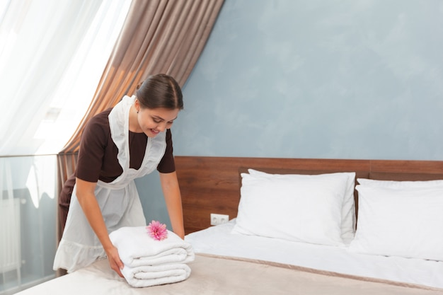 Empregada com toalhas limpas durante a limpeza em um quarto de hotel