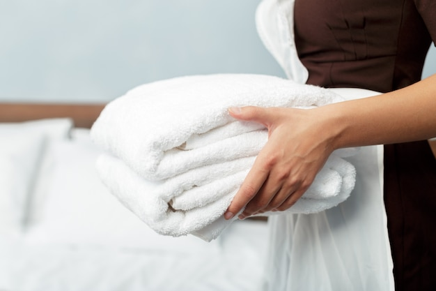 Empregada com toalhas limpas limpas durante o serviço de limpeza em um quarto de hotel