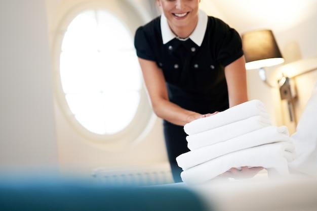 Empregada com toalhas limpas no quarto de hotel